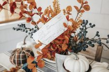an all-natural fall centerpiece of a planter with berries, bright leaves on branches and faux pumpkins on stands