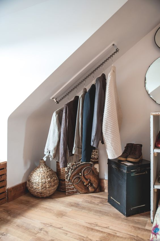 an attic space with a holder for clothes hangers attached right to the ceiling is a great way to save some space
