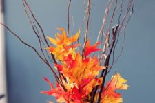 an easy and budget-friendly fall centerpiece of twigs and bright faux leaves in a vase to make last minute