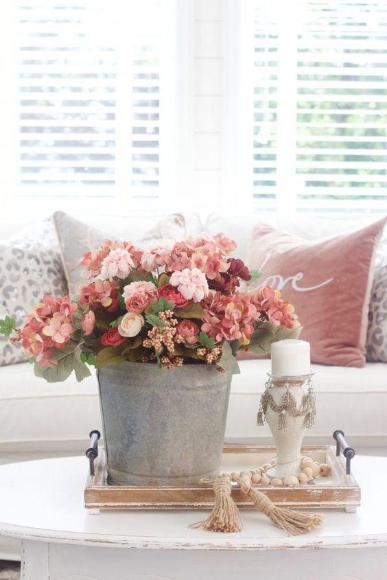 an elegant and romantic red, pink and burgundy faux flower arrangement in a bucket is a great fall decoration