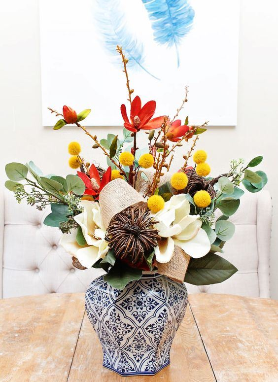 an elegant fall arrangement of leaves, billy balls, vine, burlap and faux white blooms is amazing for decor