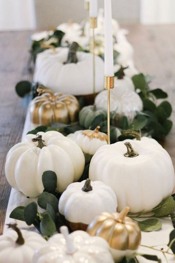 an elegant fall centerpiece of white and gold pumpkins, greenery and elegant candles in gold candleholders