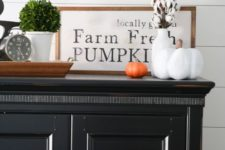 an elegant framed monochromatic sign in a stained wooden frame, some cotton and fake pumpkins