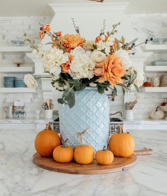 an elegant white and orange faux flower arrangement in a blue vase and orange pumpkins around it
