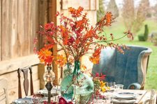 an oversized green bottle with branches with bright fall leaves and berries around is bold and cool