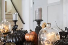black, orange and copper faux pumpkins plus a skull in a cloche make up a stylish and fun centerpiece for Halloween