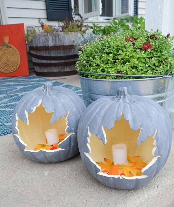 chalk painted pumpkins with cutout leaves and candles inside plus faux leaves are chic lanterns for indoors and outdoors