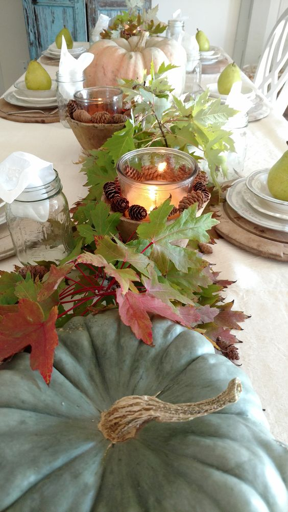 fall table decor with heirloom pumpkins, fall leaves, candle lanterns with pinecones is very cozy