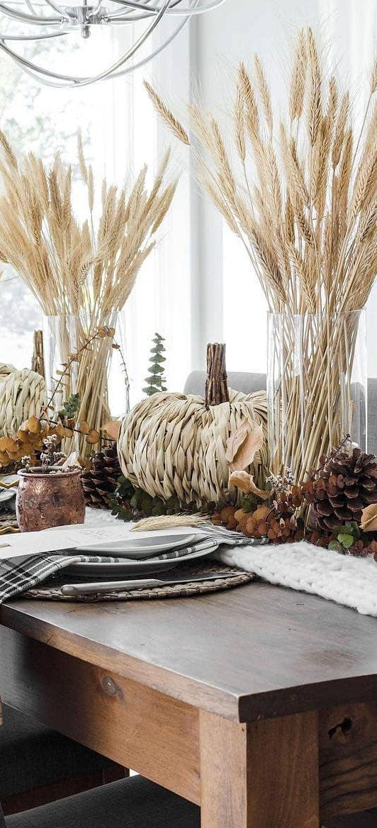 fall table decor with pinecones, leaves, dried foliage, pumpkins made of grass and wheat in glass vases