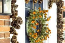 gilded pinecones covering the doorway and a dried bloom wreath make the porch very fall-like