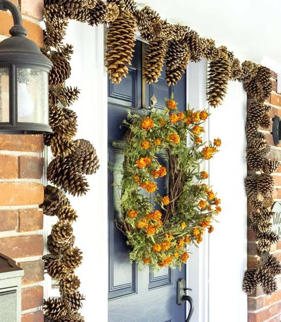 gilded pinecones covering the doorway and a dried bloom wreath make the porch very fall like