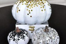 glam faux pumpkins decorated with gold, silver and black confetti to make your space very glam and chic