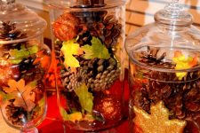jars with lids and with glitter pumpkins, leaves and pinecones are a great and easy fall decoration