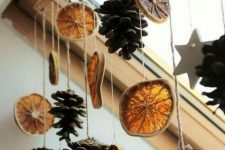 pinecones, citrus slices and stars hanging on the window is a cool natural decoration, which can be easily made