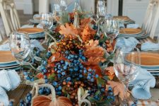 rust velvet pumpkins, berries, greenery and dried fall leaves for a large and bold fall centerpiece