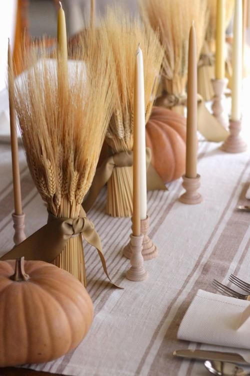 rustic fall decor with neutral candles, wheat bundles and chalked pumpkins for a vintage feel
