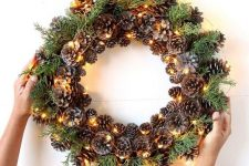 such a pinecone, evergreens and lights wreath can be a nice decoration from fall to winter and is easy to make