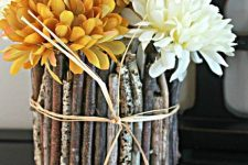 vases covered with twigs and sticks for a woodland feel and bright orange and white blooms for a fall arrangement