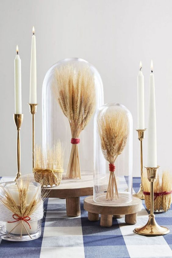 wheat bundles with red twine in cloches and on wooden stands, with candles and candle holders with wheat for fall