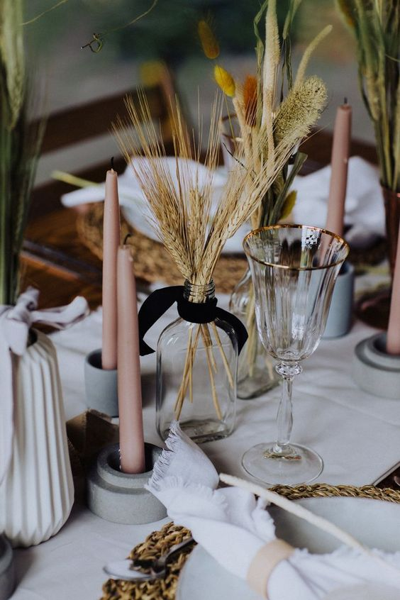 wheat in a clear bottle and pink candles for styling the table for the fall