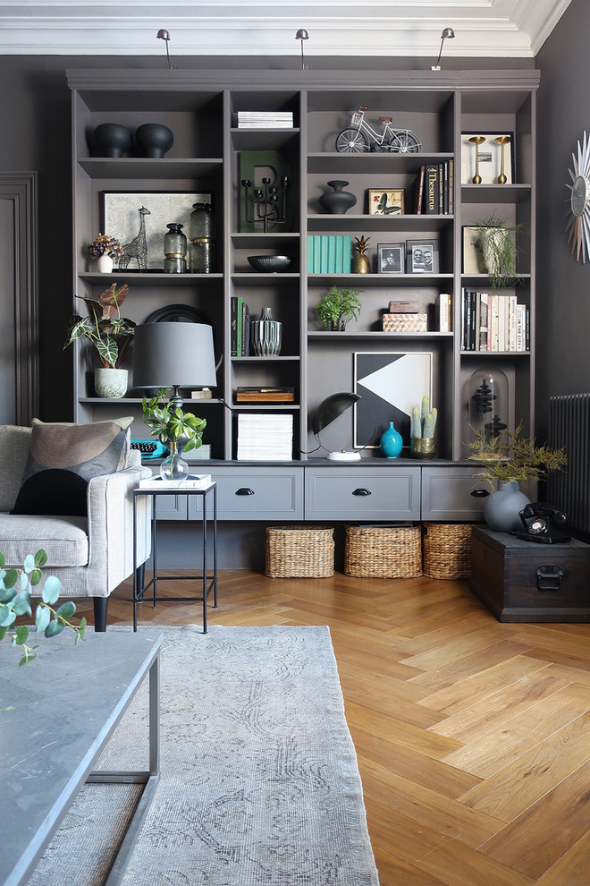 A simple set of bookshelves turned into a thing of style. Various mouldings and trims were added to cover up joints, and the whole thing was painted with a dark gray shade like walls around it. (DesignSixtyNine)