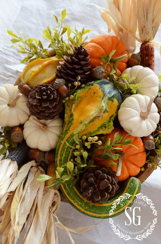 a Thanksgiving centerpiece of gourds, pumpkins, foliage, corn, acorns and pinecones