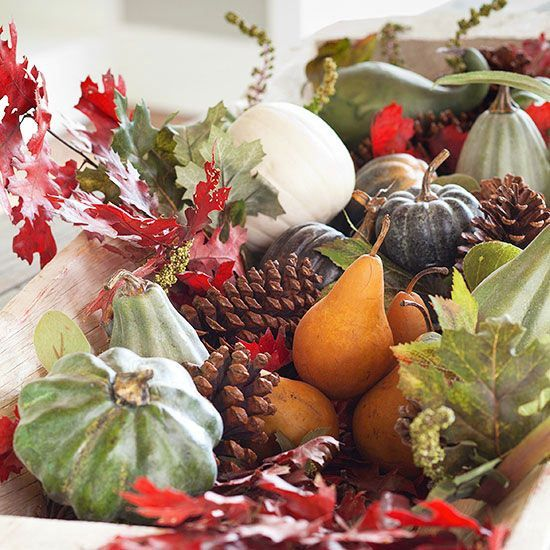 a Thanksigiving centerpiece of faux pumpkins and gourds, pears and leaves plus pinecones