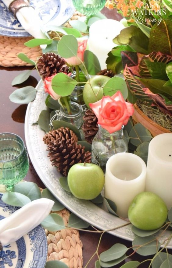 a beautiful fall centerpiece of a silver tray, green apples, pinecones, oliage and coral blooms