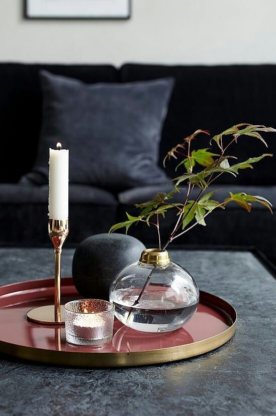 a black coffee table, a red tray, a glass candle holder, a clear vase with foliage and soem candles for an elegant feel