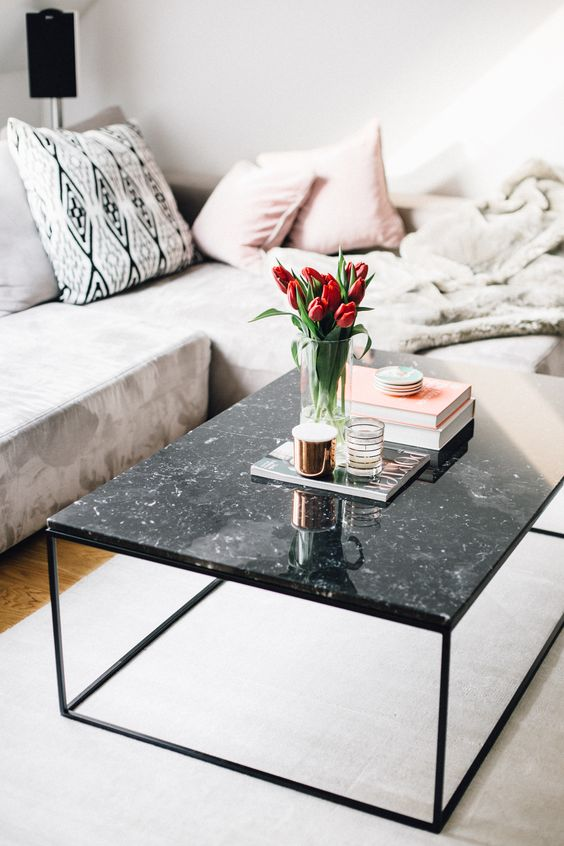 a black marble coffee table with some books, candles in candle holders and an arrangement of red tulips in a vase