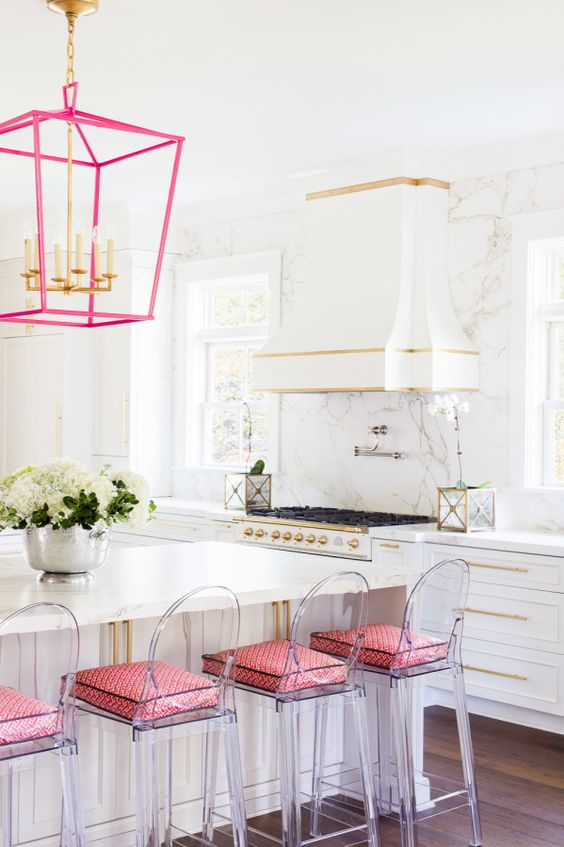a bold glam kitchen with white cabinetry, gold handles and edging, a hot pink chandelier and acrylic stools with pink cushions
