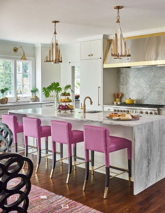 a bold glam kitchen with white cabinets, a grye backsplash and countertops, a shiny hood and metallic chandeliers, hot pink stools and gold fixtures