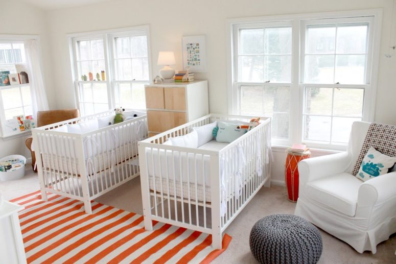 a bright and fun shared nursery done with IKEA Sundvik cribs, bold orange and turquoise touches, soem cozy chairs and cabinets