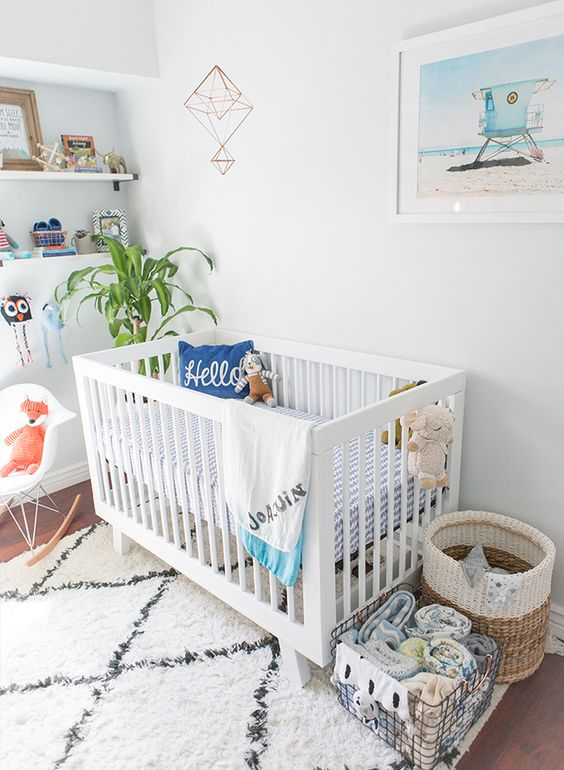 a bright beach inspired nursery with a white Sundvik crib, baskets, open shelving, a beach artwork and some printed textiles