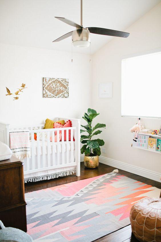 a bright boho nursery with a colorful rug, books, a leather ottoman and artworks plus an IKEA Sundvik crib