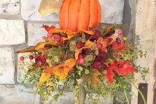 a bright faux pumpkin with lots of faux leaves, greenery and berries placed on a wooden stand