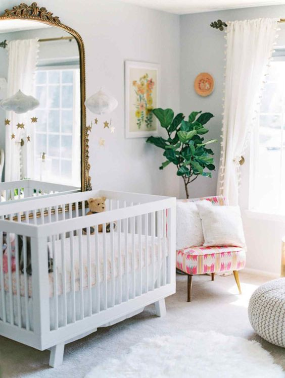 a bright nursery with an IKEA Sundvik crib, a statement mirror in a vintage frame, a bright chair, potted plants and a knit ottoman