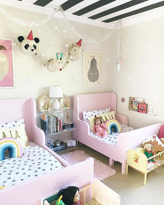 a bright shared girls' bedroom with pink IKEA Sundvik beds, faux animal heads, bright toys and banners
