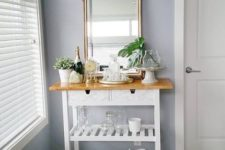 a chic IKEA Forhoja cart done with marble contact paper, with a wooden countertop as a small home bar