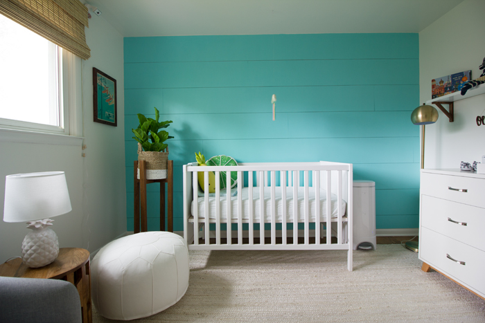 a chic and bright nursery with a statement turquoise wall, a white IKEA Sundvik crib and leather ottoman, wicker shades and a potted plant