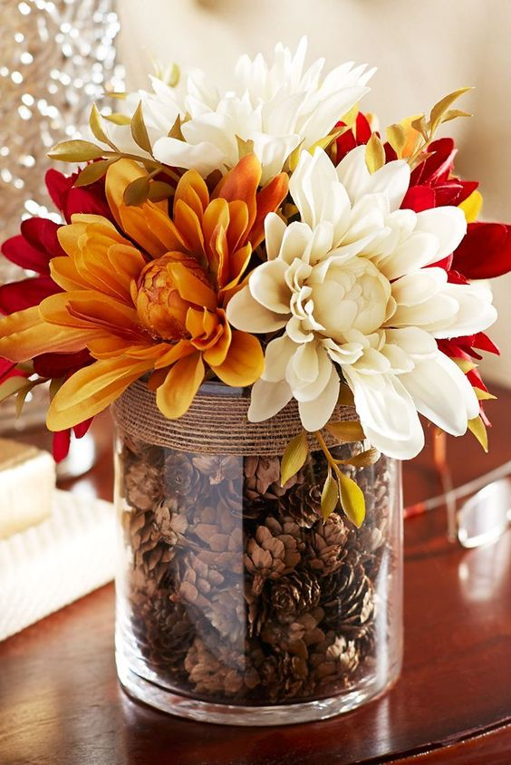 a chic fall centerpiece of a clear vase filled with pinecones, burlap and bright fall blooms