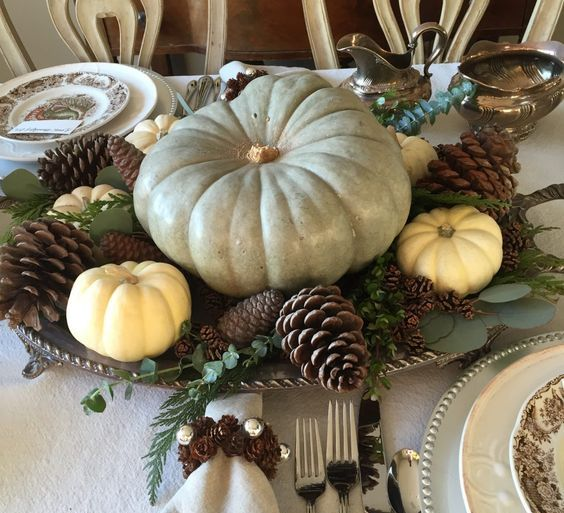 a chic fall centerpiece of a vintage tray, foliage, pinecones, white pumpkin and a giant heirloom one
