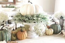 a chic fall centerpiece of a white pumpkin with lots of greenery on a white stand and faux pumpkins on the table