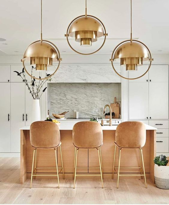 a chic glam kitchen with white cabinetry, peachy stools with gold legs, a peachy kitchen island and copper pendant lamps