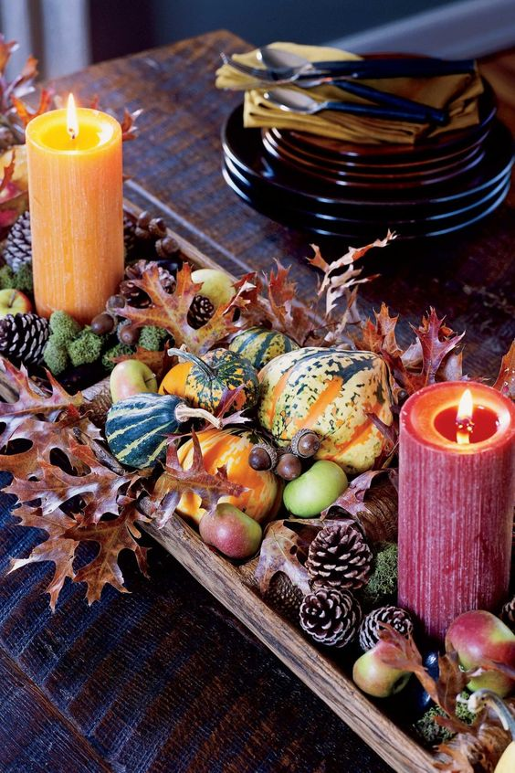 a colorful harvest centerpiece of pinecones, apples, leaves, moss, gourds and colorful candles