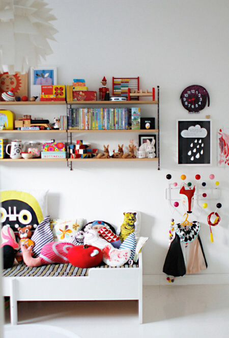 a colorful kid's room with lots of artworks, a large bookshelf, toys, pillows and a white Sundvik bed