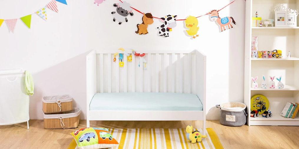 a colorful nursery with a Sundvik crib, bright animal garlands, toys, a storage unit and baskets