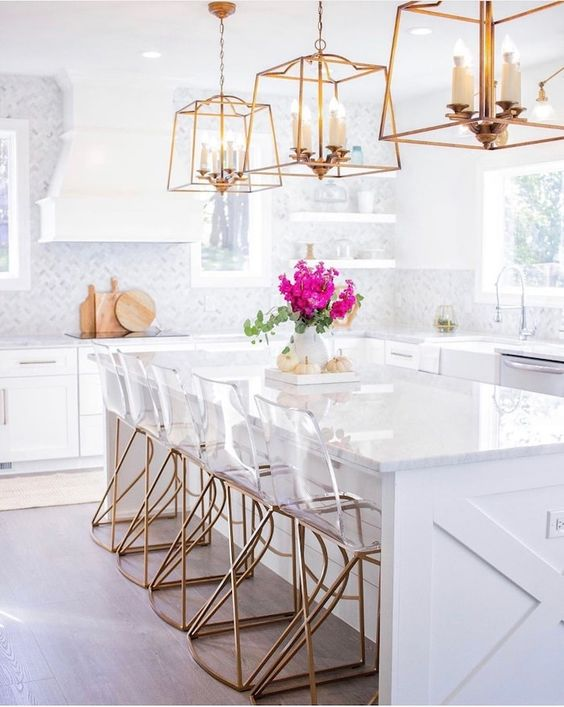 a contemporary glam kitchen with white cabinetry, white marble tiles, glam brass chandeliers and acryl and brass chairs