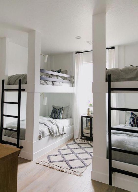 a contemporary neutral kids' room with two bunk bed units, metal ladders and wall lamps over each bed