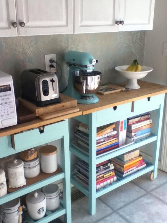 a cooking kitchen area made of two IKEA Forhoja carts in light blue, with wooden countertops is very space-saving